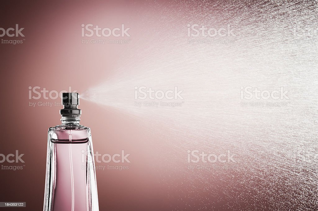 Glass bottle of perfume spraying mist against pink background stock photo