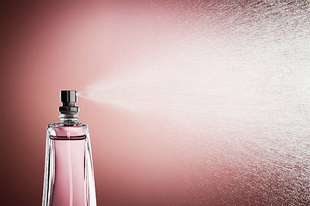 glass bottle of perfume spraying mist against pink background - scented stock photos and pictures
