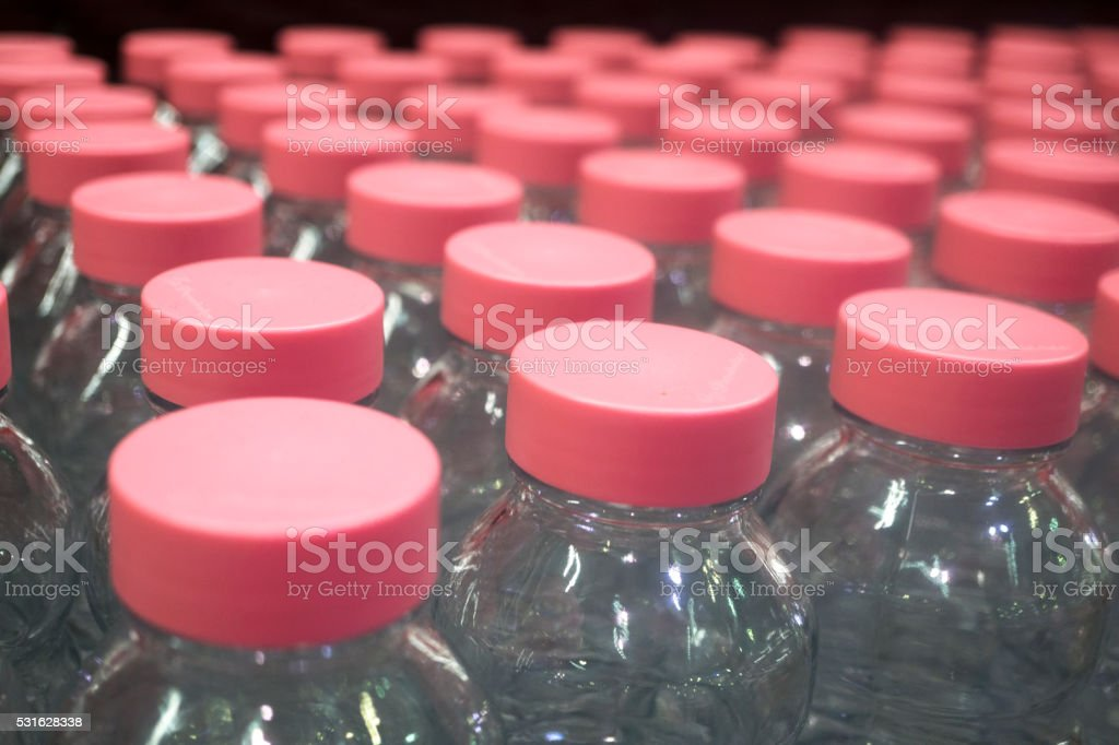 Glass Bottle of pink lids , close up stock photo
