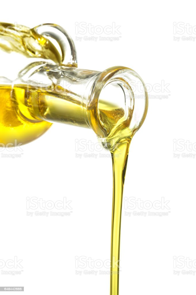 glass bottle pouring oil isolated on white stock photo