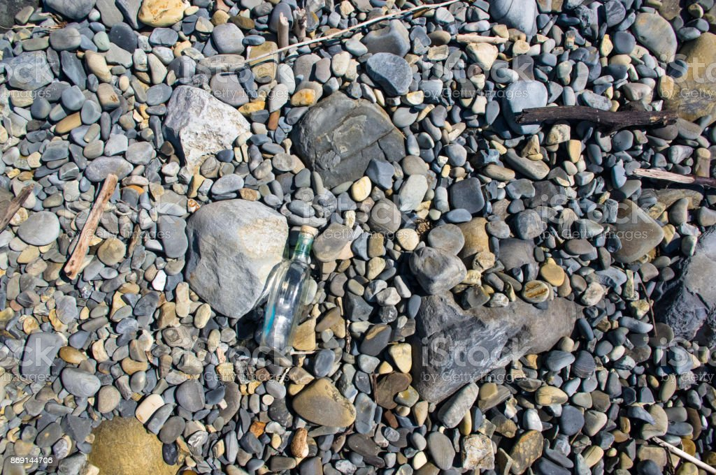 glass bottle washed up by the sea stock photo