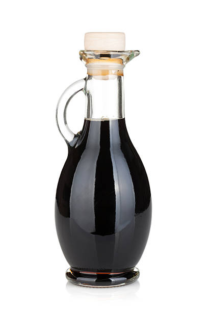 Glass bottle with handle full of black liquid Vinegar bottle. Isolated on white background balsamic vinegar stock pictures, royalty-free photos & images