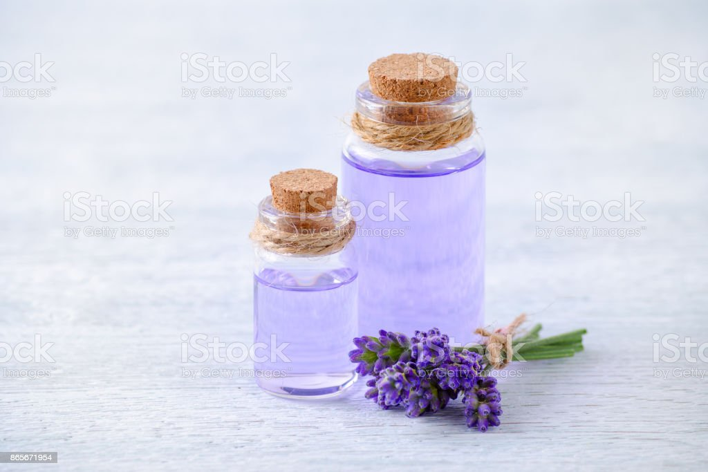 glass bottles aromatherapy oil and fresh lavender flowers on wooden table