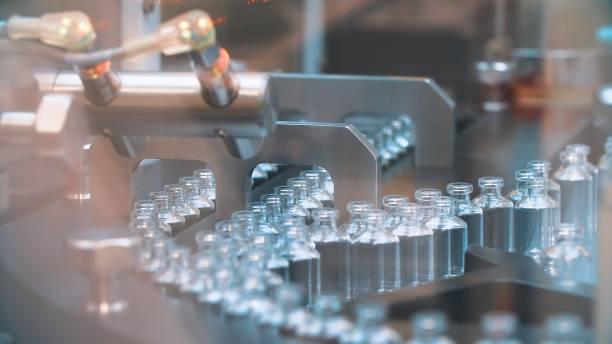 glazen flessen in productie in de lade van een automatische vloeibare dispenser, een lijn voor het vullen van geneesmiddelen tegen bacteriën en virussen, antibiotica en vaccins - naald chirurgisch instrument stockfoto's en -beelden