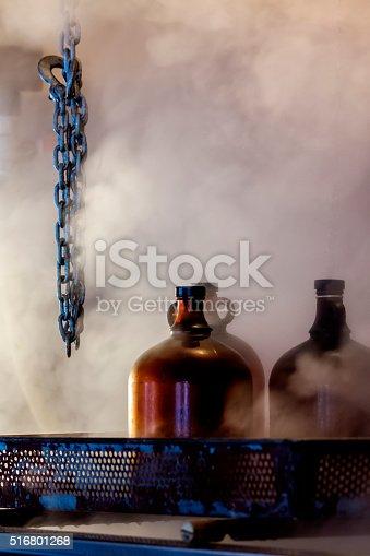 Trois bouteilles de verres. Une grosse chaîne suspendue. Vapeur ambiante.