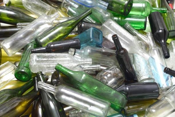 glasflaschen in einer glas-recycling container - recycelte weinflaschen stock-fotos und bilder
