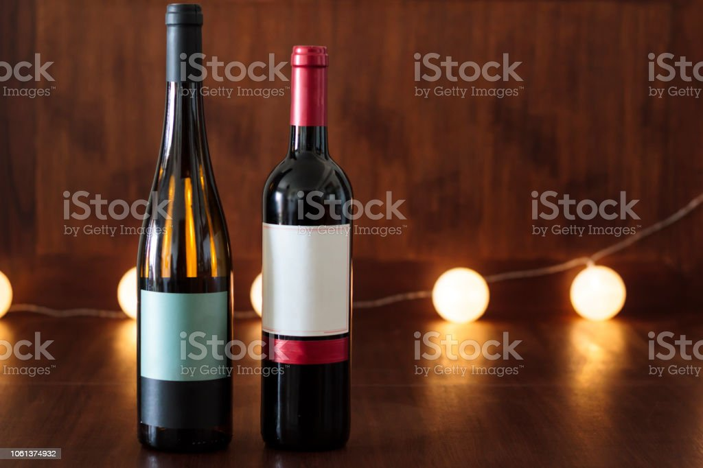 Glass bottles of red and white wine on wooden table with lights on...