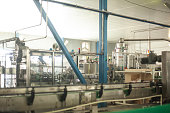 Glass bottles on the automatic conveyor line at the champagne, beer or wine factory. Plant for bottling alcoholic beverages.