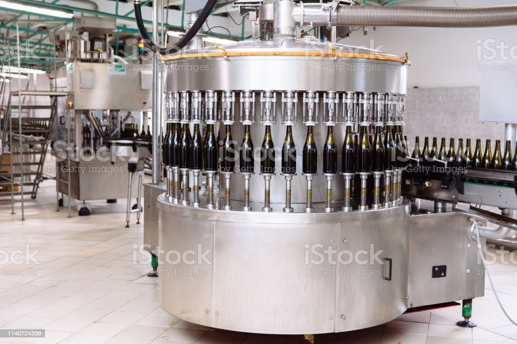Glass bottles on the automatic conveyor line at the champagne or wine...