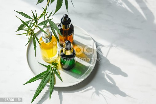 istock Glass bottles with CBD oil, THC tincture and hemp leaves on a marble background. Flat lay Cosmetics cannabis oil. 1172961154