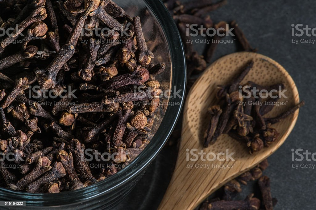 Glass Bowl and Wooden Spoon of Cloves stock photo