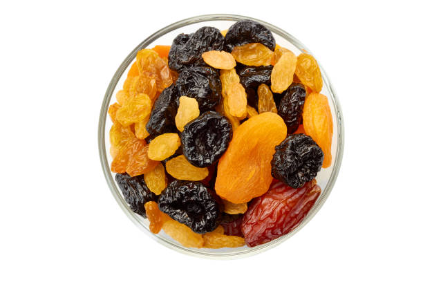 glass bowl of dried fruits mix on white - dried fruit stock photos and pictures