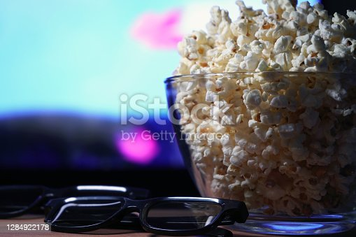 glass bowl of popcorn and 3D glasses in the background a TV is running. In the evening, we watch movies sitting at home on self-isolation due to the covid-19 pandemic.