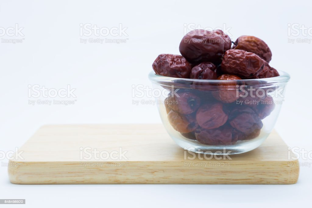 Glass bowl red dry jujube on wooden board stock photo