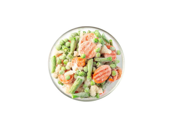 Glass bowl with frozen vegetables isolated on white, top view stock photo