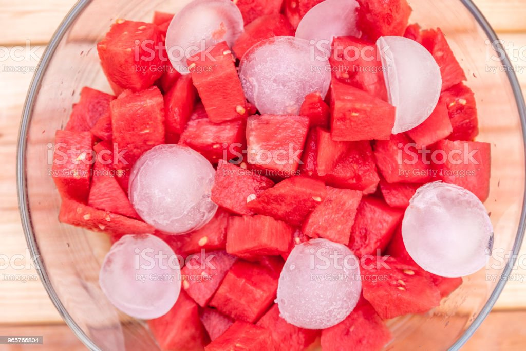 glass bowl with pieces of watermelon and cubes on wooden table - Royalty-free Bowl Stock Photo