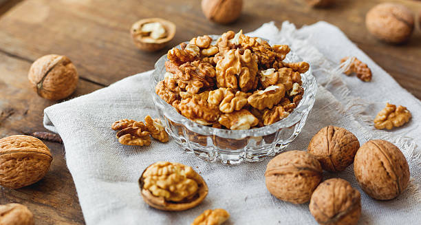 Glass bowl with walnuts on rustic homespun napkin. Healthy snack. stock photo