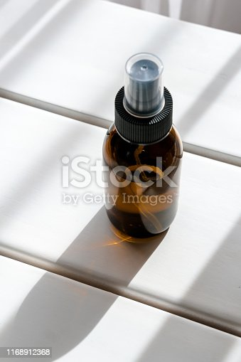 1167558793 istock photo Glass brown spray bottle with liquidmetics 1168912368
