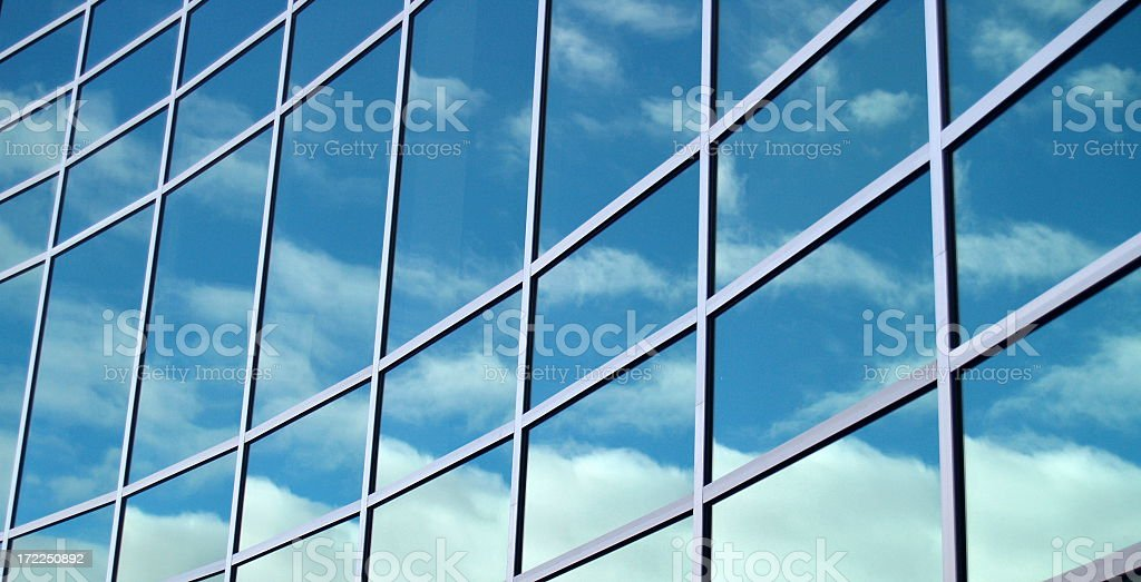 Glass building reflecting blue skies and clouds royalty-free stock photo