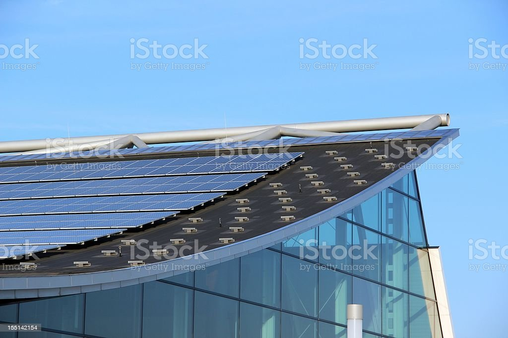 Glass building with solar panels on the roof stock photo