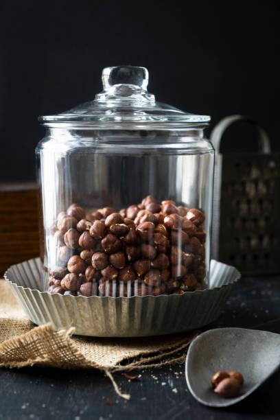 Glass Canister of Shelled Hazelnuts on Black stock photo