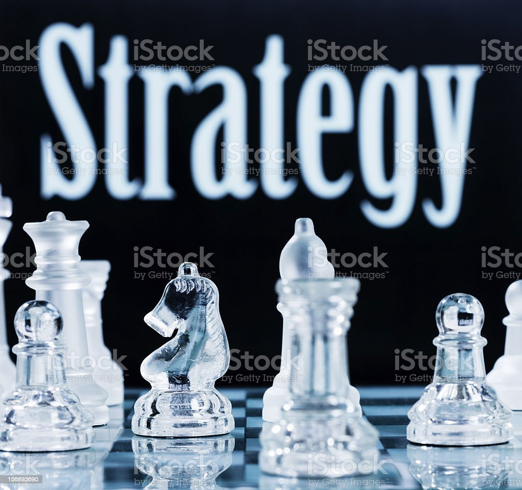 "Glass chess pieces in front of sign saying ""Strategy"" royalty-free stock photo"