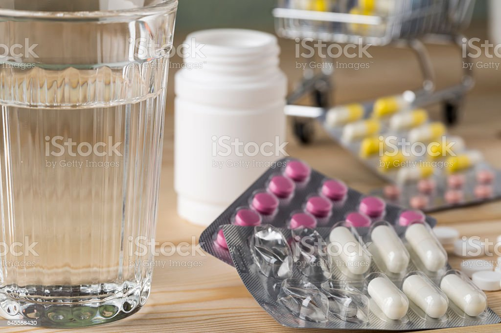 Glass clean water and bunch blister packs of pills stock photo
