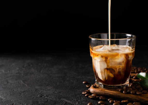 vidrio frío colar el café con hielo y leche sobre fondo negro u oscuro - frío fotografías e imágenes de stock