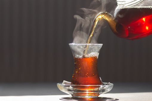 Glass cup of brewed black turkish tea, traditional hot drink concept