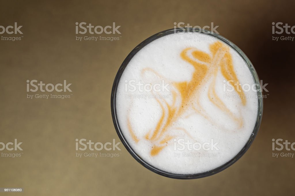 Glass cup of coffee with cream close-up on gold background. Cappuccino, Latte. View from above
