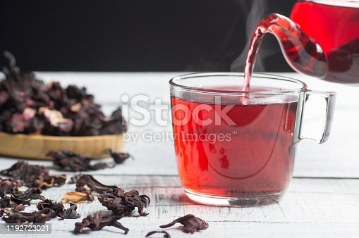 istock Glass cup of healthy hibiscus tea pouring from the teapot with dried hibiscus flowers on white wooden background, winter hot drink concept for cold and flu 1192723021