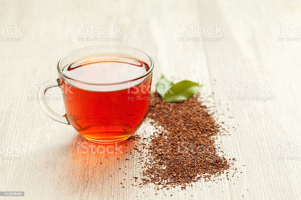 Glass cup of healthy natural herbal rooibos tea on wooden stock photo