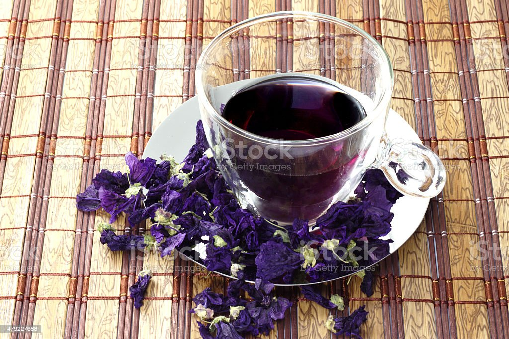 Glass cup of herbal tea with dry mauve flowers. stock photo