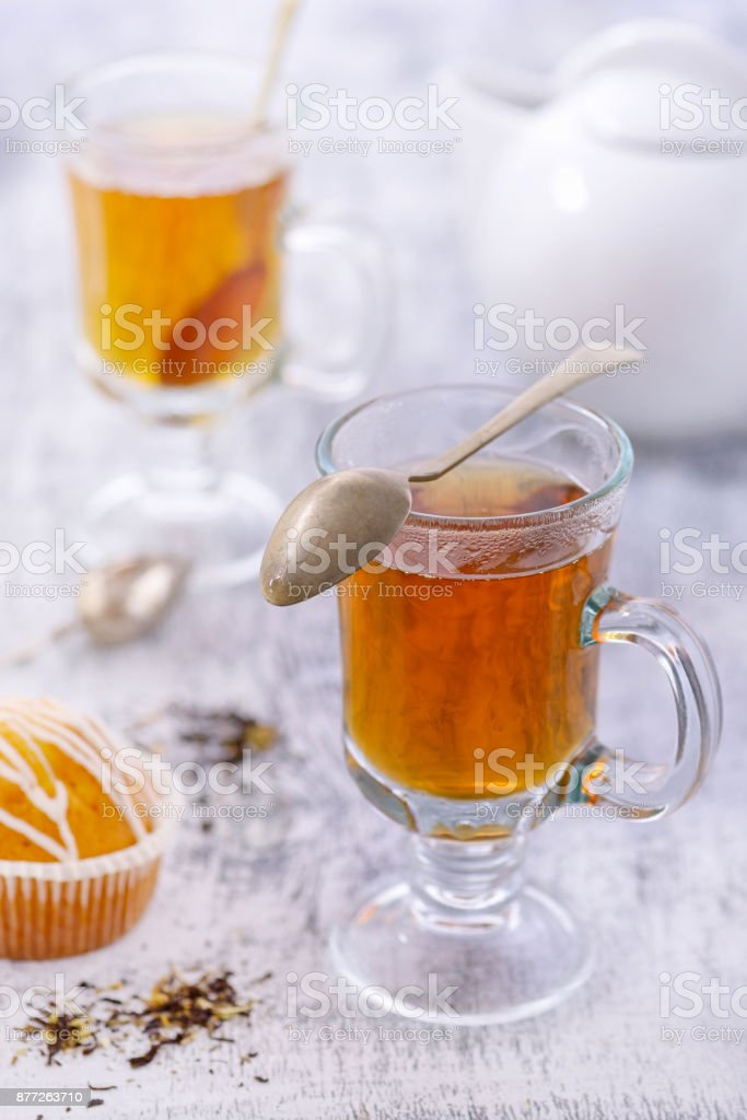 Glass cup of hot tea on white table stock photo