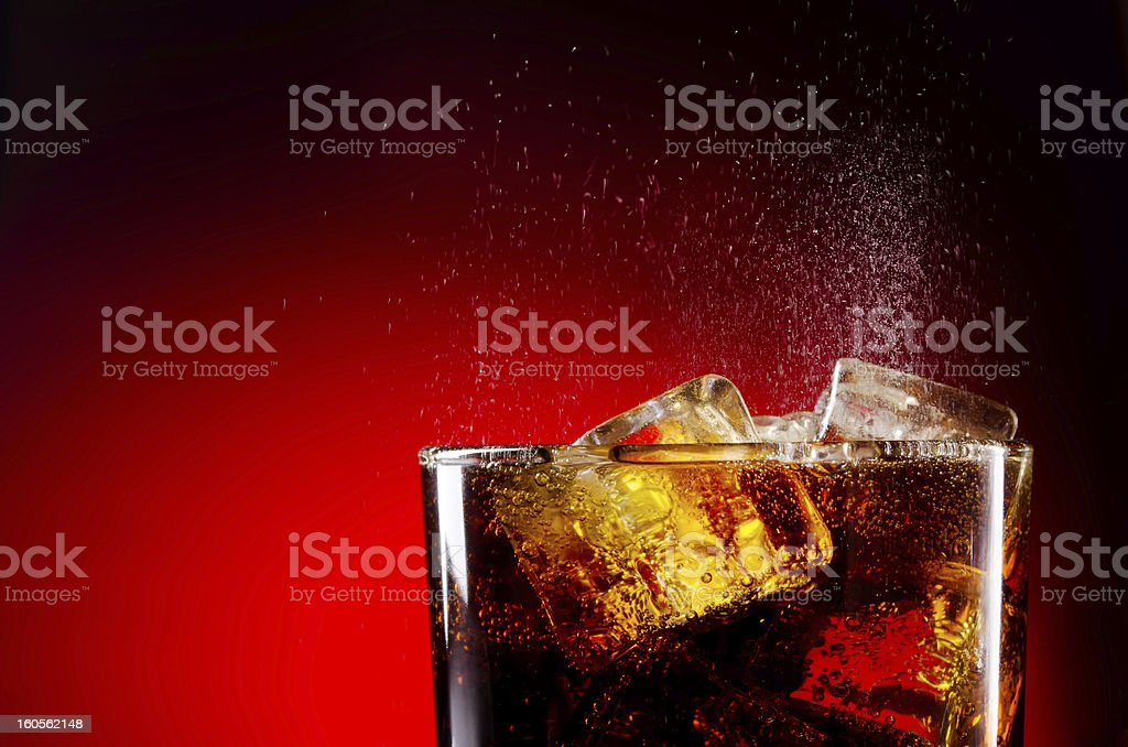 Glass cup of iced cola on red background stock photo