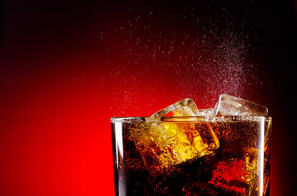 glass cup of iced cola on red background - cola stockfoto's en -beelden