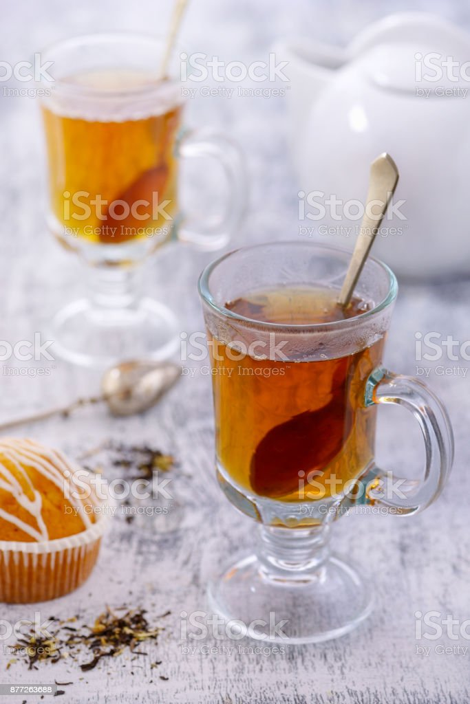 Glass cup of tea on white table with cupcake stock photo