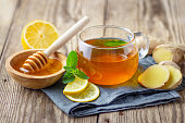 A glass cup of tea with lemon, mint, ginger and honey on wooden rustic table.