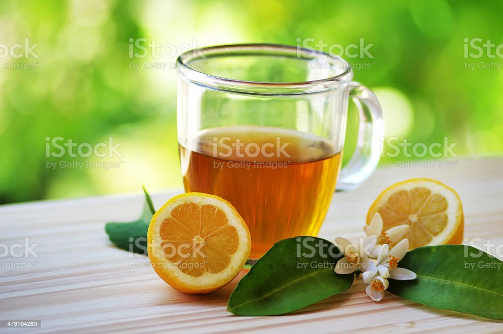 Glass cup of tea with lemon on table stock photo
