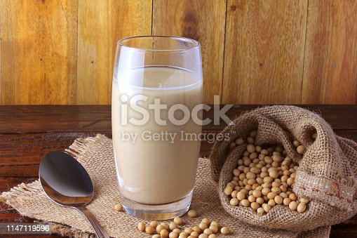 887350996 istock photo glass cup with fresh soy milk and grains in a rustic bag on wooden table. Front view. Horizontal Composition 1147119596