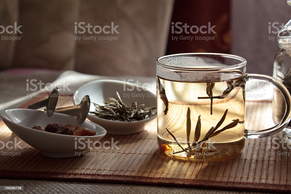 A glass cup with hemp tea and white bowls on a wooden table stock photo