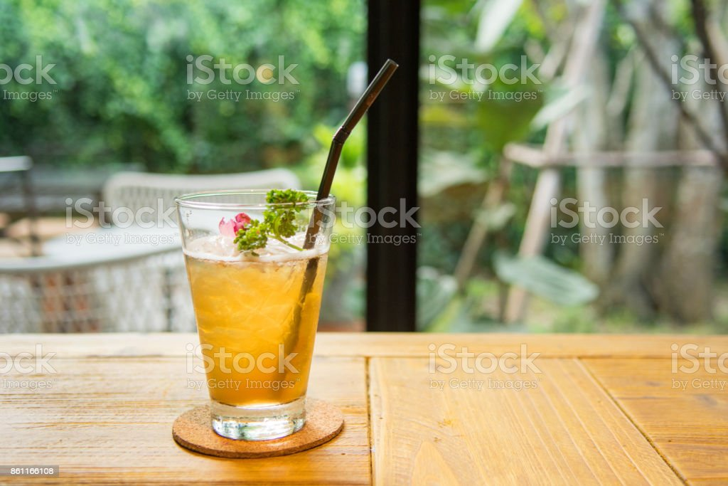Glass cup with ice fresh rose tea and dry roses on wooden table stock photo