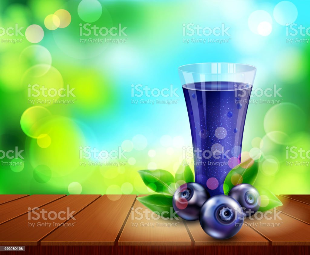 glass cup with juice of blueberries standing on a wooden table on the background of the sky and green foliage stock photo