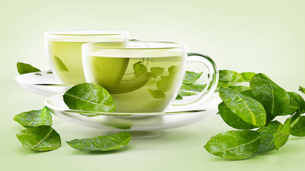 Glass cups with green tea and tea leaves isolated on white stock photo