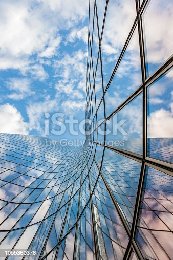 Glass curved building reflecting blue sky and white clouds low angle view