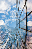 istock Glass curved building and blue sky 1055360376