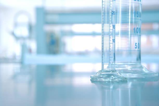 glaszylinder in chemie wissenschaft labor forschungshintergrund - messzylinder stock-fotos und bilder