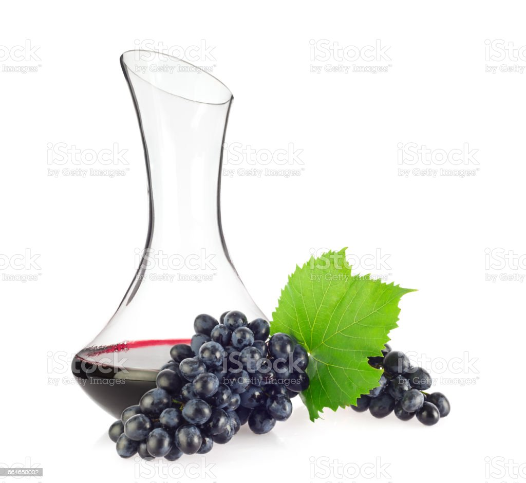 Glass decanter with red organic wine, blue grapes and green leaf stock photo