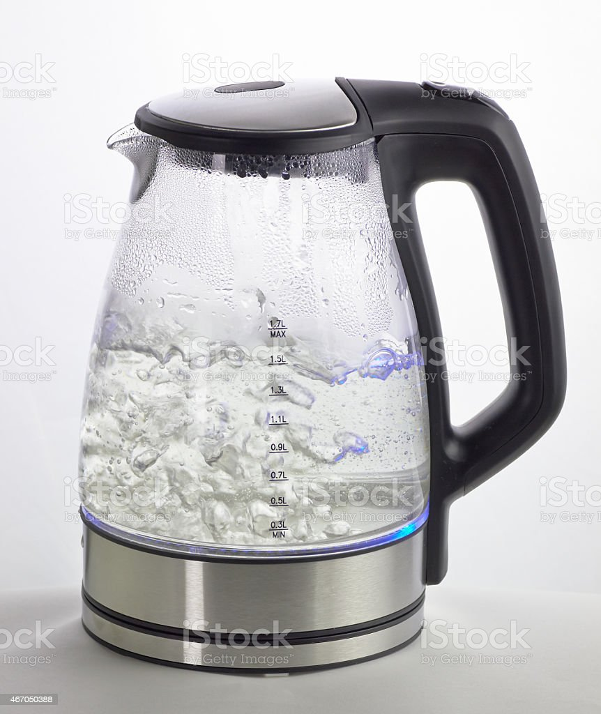 A glass electric kettle with boiling water inside stock photo