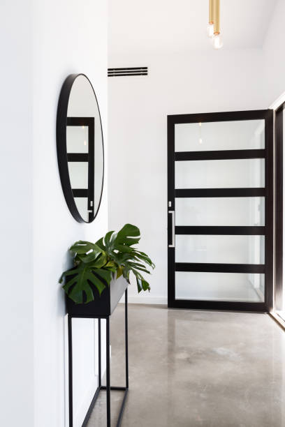 Glass entry door to foyer with planter and round mirror stock photo